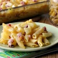 Ham and Pineapple Pasta Baked in a glass baking dish, served on a green sharing plate