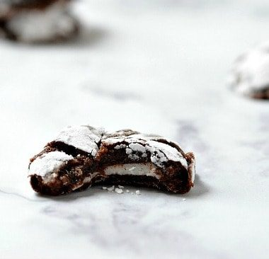 Peppermint Patty Stuffed Chocolate Crinkle Cookie. Topped with powdered sugar. Displayed on a marble countertop