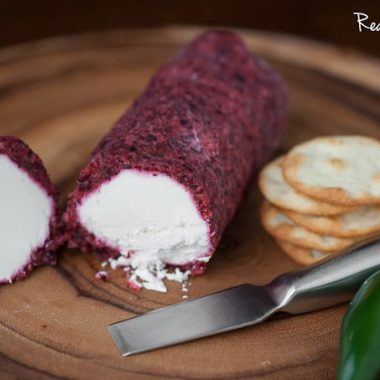 Jalapeño Cranberry Cheese Log cut in half with a side of crackers