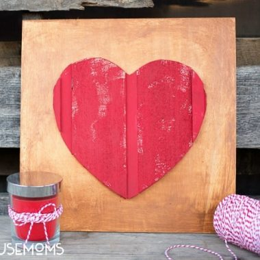 DIY Wood Heart Art. Wood plaque with wood red painted heart in he middle. Red candle off to the side of the photo with a white and red string as a bow.