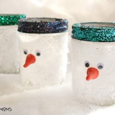 Snowman Mason Jars. Mason jars covered in fake snow tops painted in glitter. Orange cran tip for the snowman's nose
