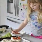 Bread maker pizza dough. little girl topping Mini pizza's with tomato sauce
