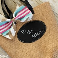 "$1 Spot DIY Personalized Beach Tote. Straw sack with black handles, large chalkboard label on the front that reads ""To the beach"" an oversized burlap bow in Spring or Summer colors."