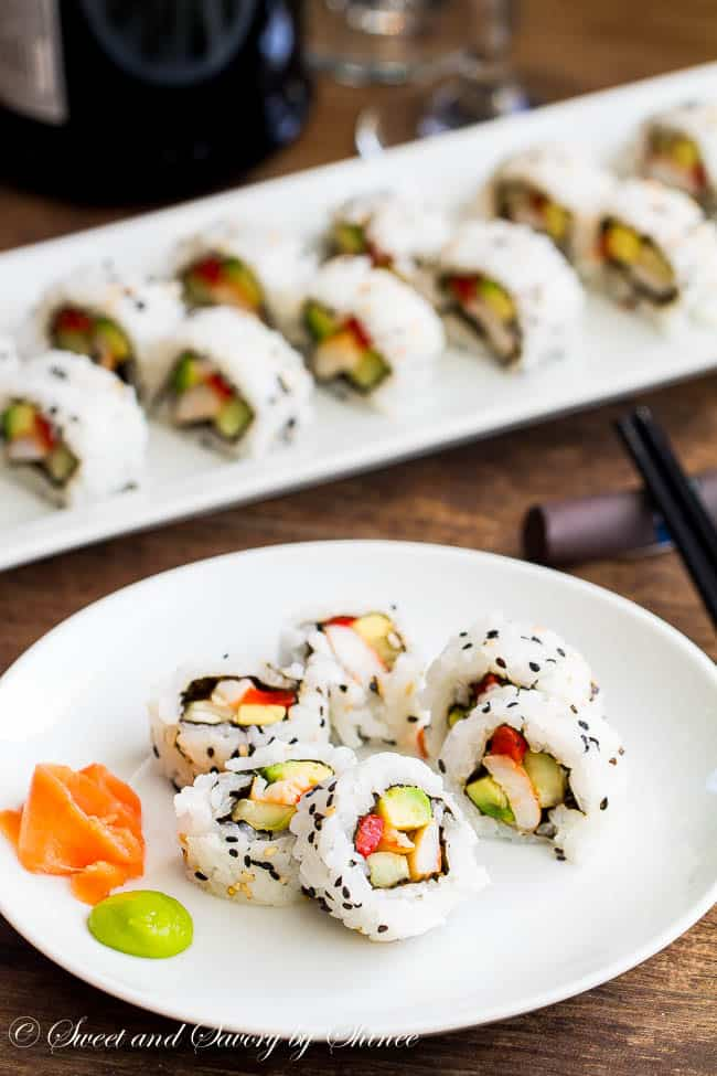 Homemade sushi rolls. white rice as the base of the roll. served on large white serving dish and round white plate