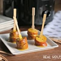 Slow Cooker Honey Mustard Kielbasa Bites. served on a white serving dish with minni wooden forks