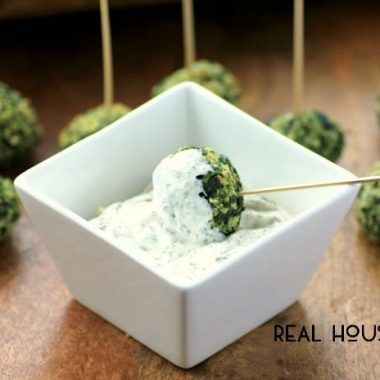 Spinach Balls with panko crumbs served with a side of lemon dip. Toothpicks at the top of the spinach balls for easy grabbing