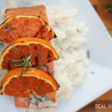 Grilled Orange-Rosemary Salmon, on a bed of white rice topped with orange slices