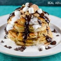 S'Mores Chocolate Chip Pancakes with chocolate ganache and marshmallow syrup are a fun, decadent breakfast that the whole family will love!