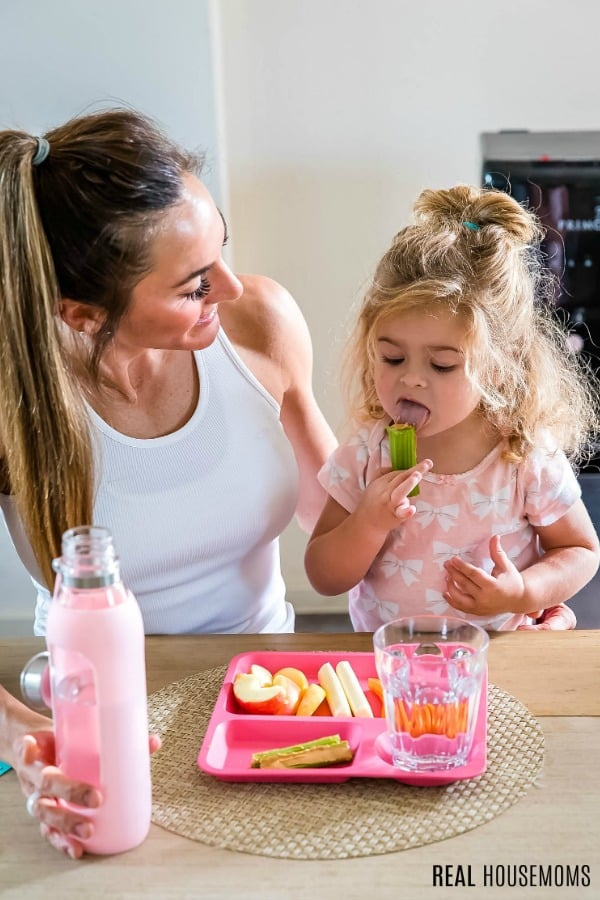 little girl sitting with her mom while licking peanut butter off celery