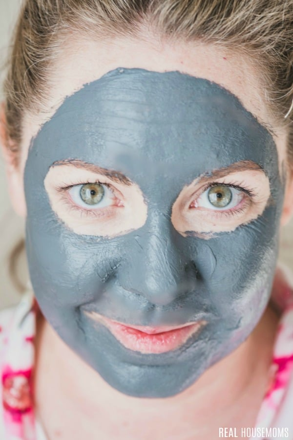 woman's face with gray face mask cream on