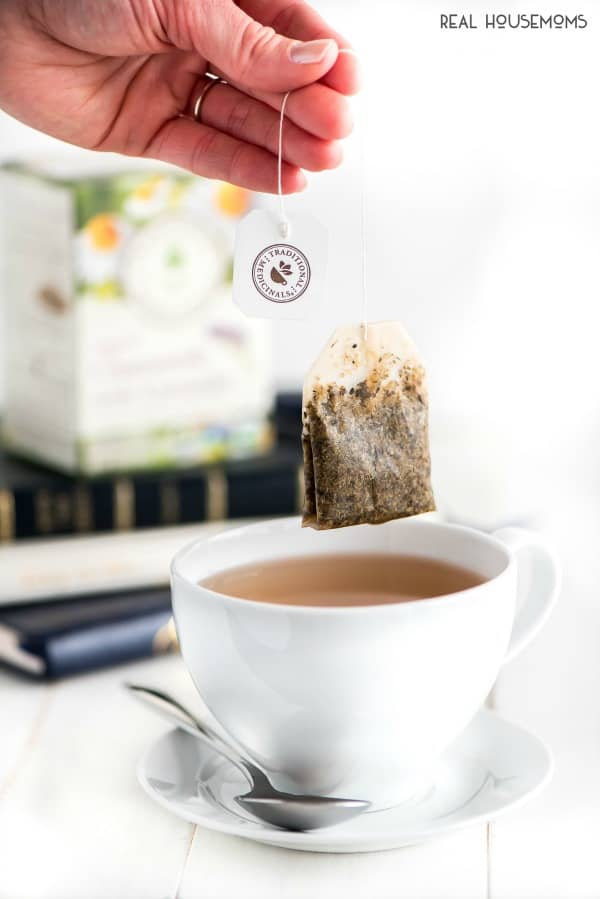 tea bag being lifted out of a cup up tea after steeping