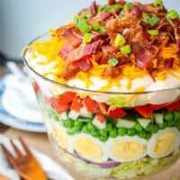 Classic 7 Layer Salad is an easy, make-ahead recipe perfect for a crowd! With crisp veggies and tangy dressing layered on top, it's a potluck favorite!
