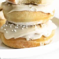 three air fryer coffee donuts stacked up with a bite taken out of the top donut with recipe name at the bottom
