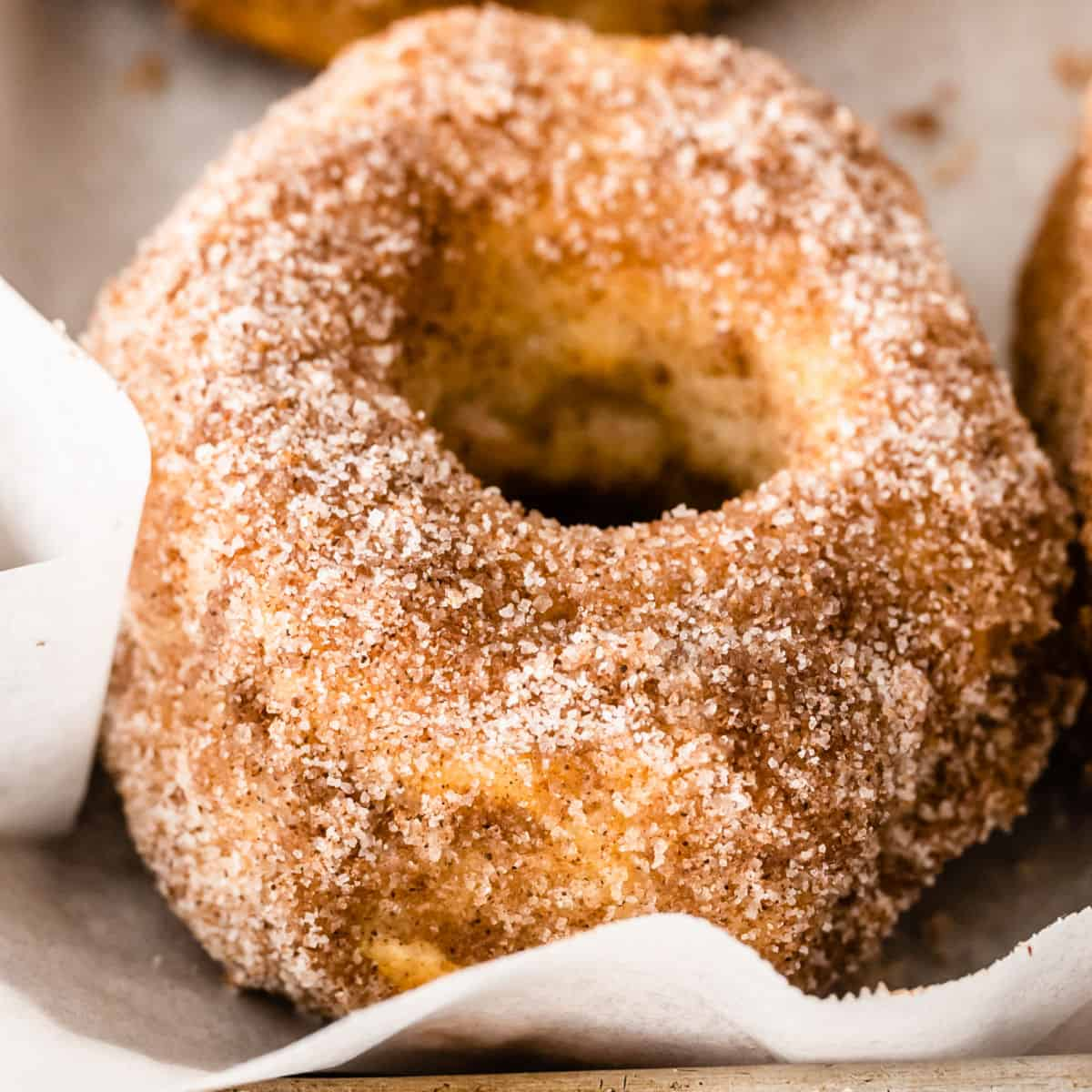 square close up image of a cinnamon-sugar air fryer donut on a baking sheet with parchment paper