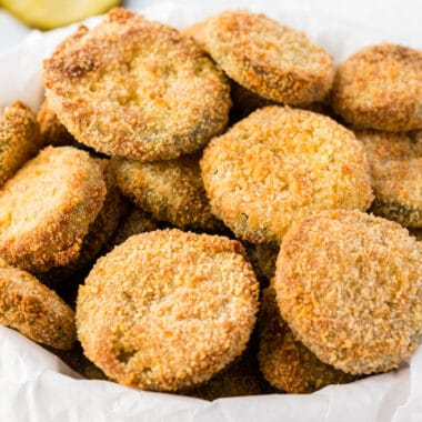 square image of air fryer fried pickles in a bowl with parchment paper