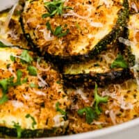 air fryer parmesan zucchini on a plate with recipe name at the bottom