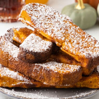 square image of air fryer pumpkin french toast sticks with powdered sugar