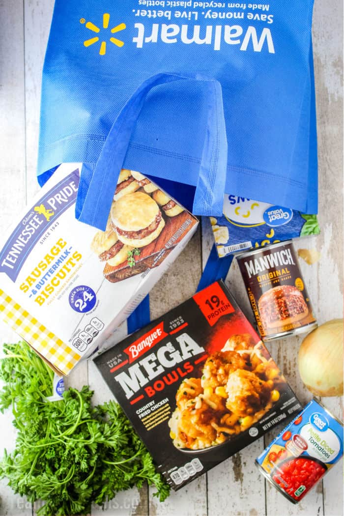 walmart shopping bag with manwich sauce, banquet country chicken fried microwave meal bowl, frozen Tennessee Pride sausage & biscuits, onion, parsley, canned diced tomatoes, and pasta