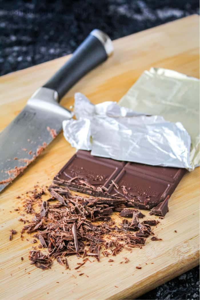 chocolate bar and knife on a cutting board with chocolate cut to make chocolate shavings