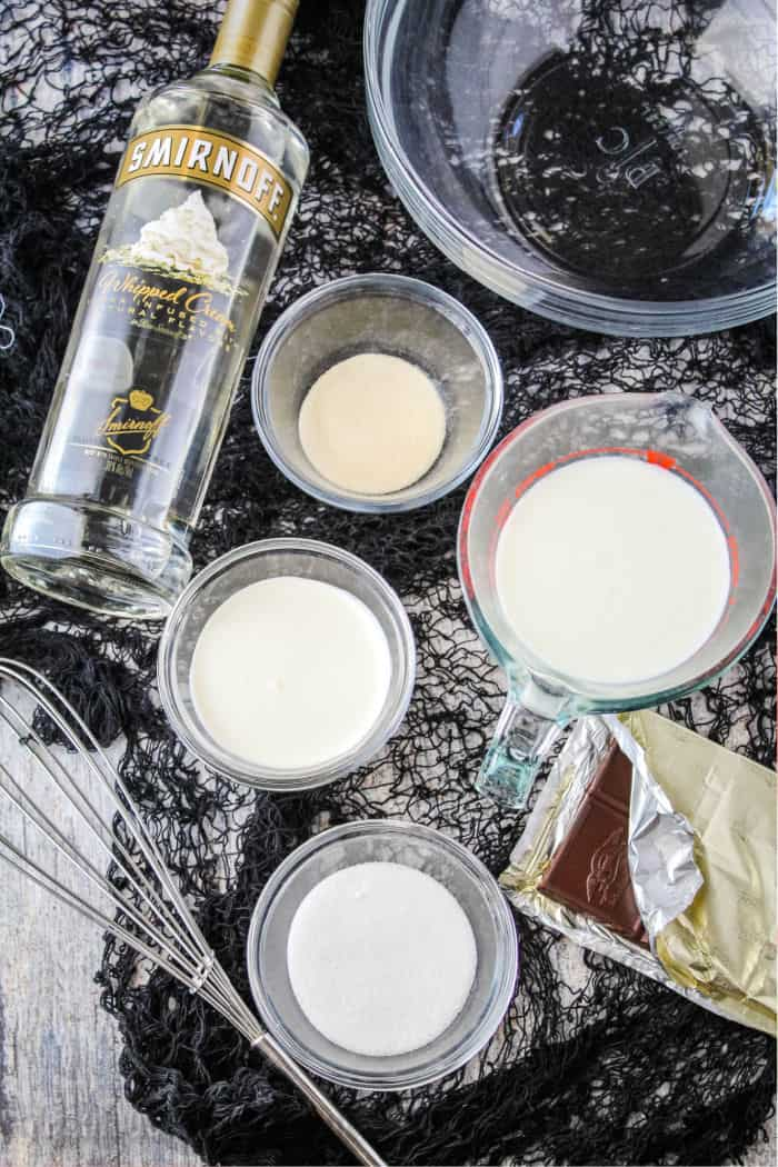 ingredients to make jello shots next to a mixing bowl and whisk