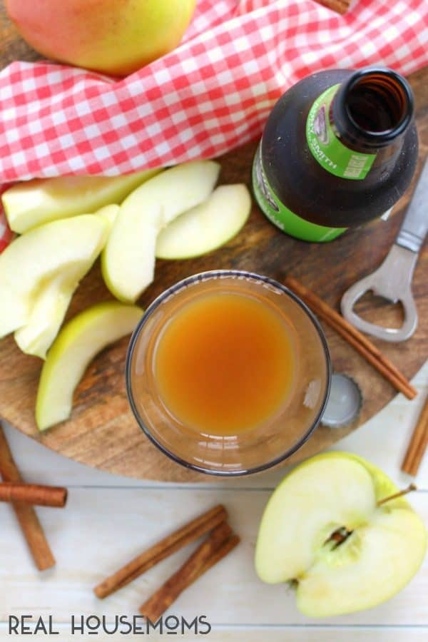 Over head shot of Apple Cider Shandy being assembled in a pint glass with a beer bottle, cinnamon sticks and apple slices around the table