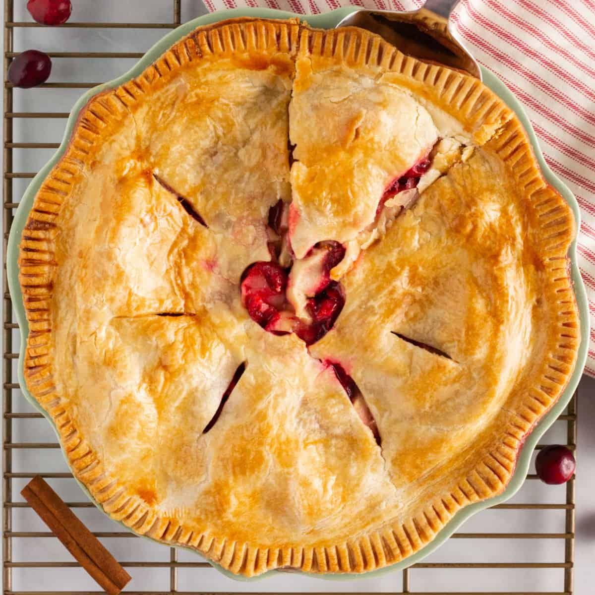 square image of apple cranberry pie in a pie plate with a pie serve starting to remove a slice