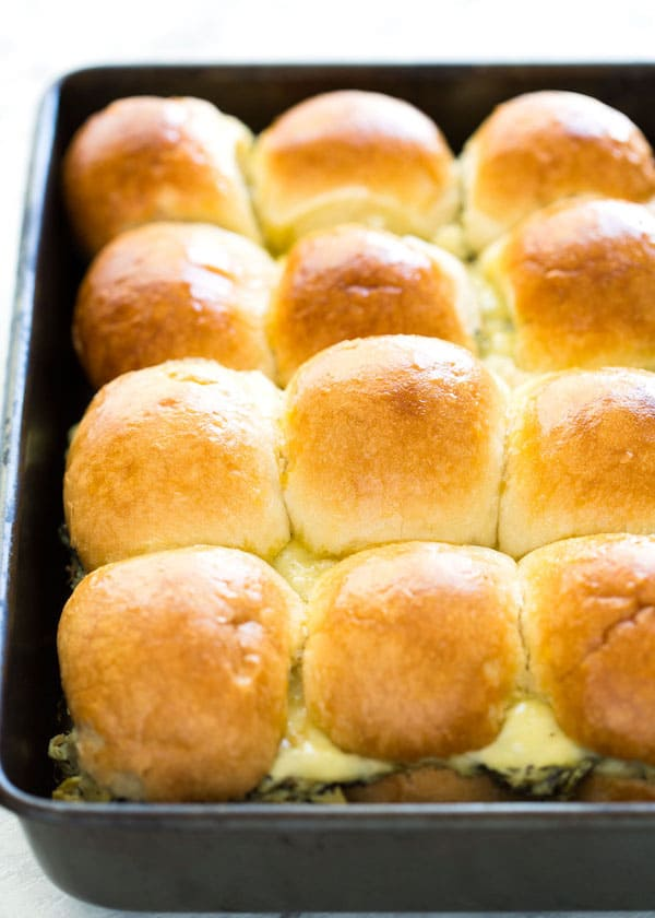 A pan of cooked Spinach Artichoke Dip Sliders with golden topped rolls