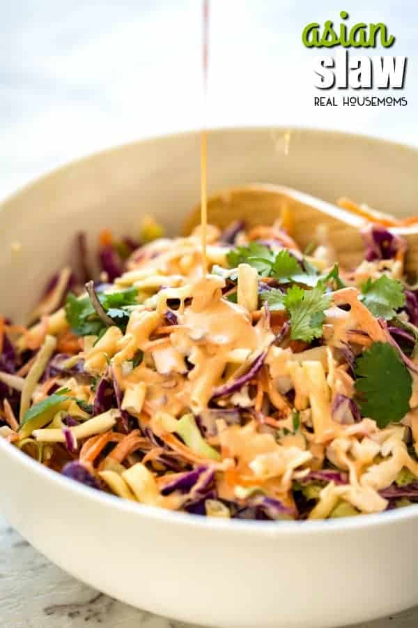 Dressing being pour over Asian Slaw