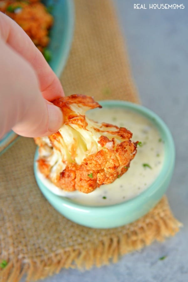 BBQ Cauliflower bite being dipped in a small bowl of ranch dressing