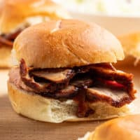 close up of a BBQ pork loin slider with sliced meat and BBQ sauce