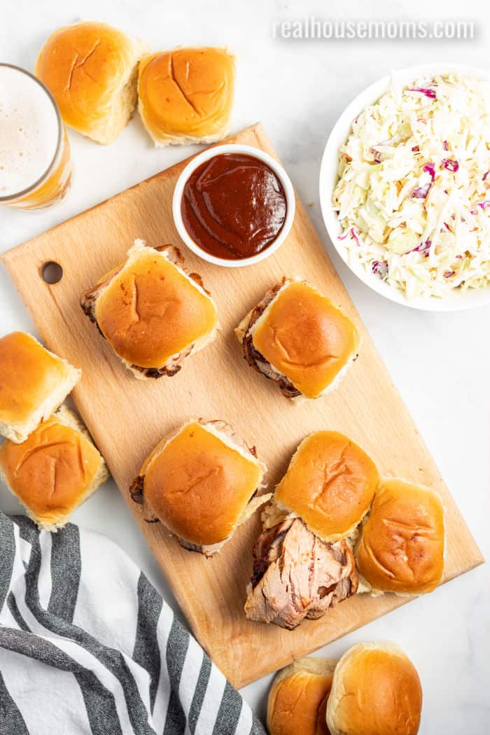 dinner rolls on a cutting board topped with sliced grilled pork loin next to a cup of bbq sauce and bowl of cole slaw