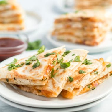 BBQ Chicken Quesadillas are a fun twist on a delicious pizza! Stuffed with shredded chicken, lots of cheese, and BBQ sauce they'll be the star of any party!