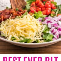 BLT salad in a serving bowl before tossing together with dressing with recipe name at bottom