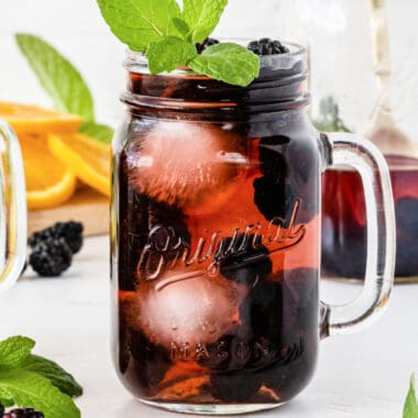 square image of blackberry sangria in a mason jar glass with mint