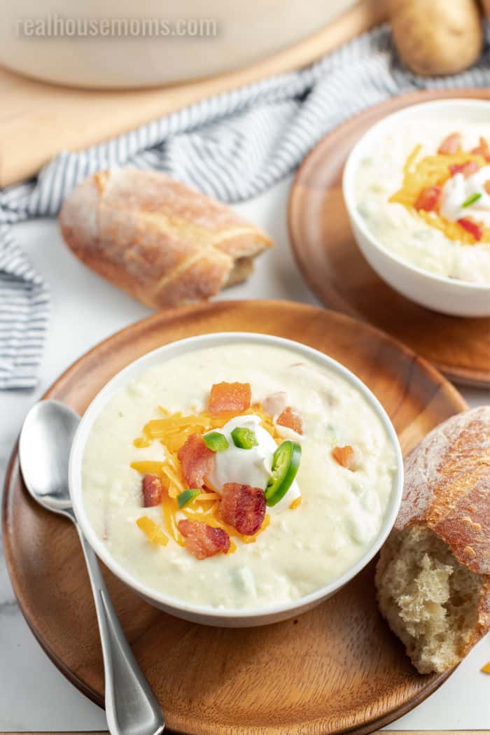 bacon jalapeno potato soup in a bowl with cheese, bacon, and sour cream