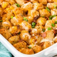bacon ranch tater tot casserole in a baking dish with recipe name at the bottom