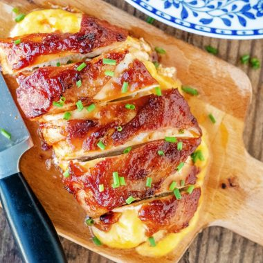 Bacon Wrapped Chicken slathered with sticky BBQ sauce & stuffed with gooey, melted cheese is an easy dinner idea that'll have everyone asking for seconds!