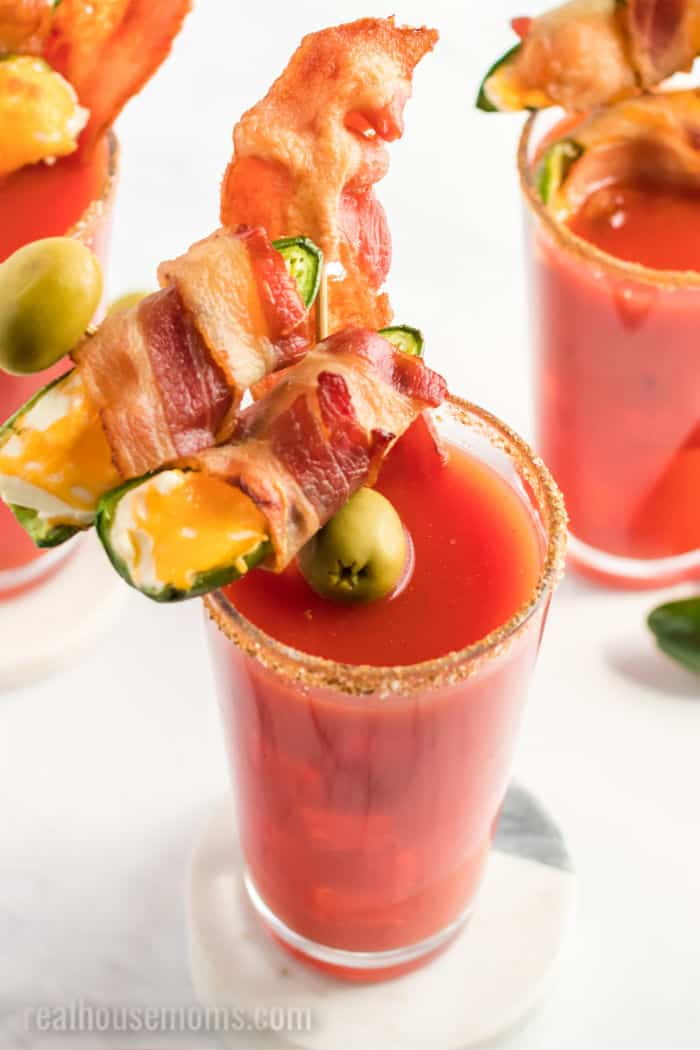 looking down in a bloody mary garnished with bacon and a jalapeno popper