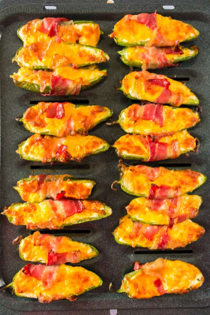 bacon wrapped jalapeno poppers on a broiler pan after cooking
