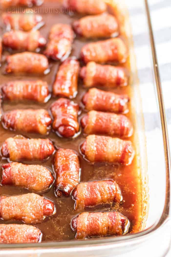 bacon wrapped little smokies in a baking dish with brown sugar sauce