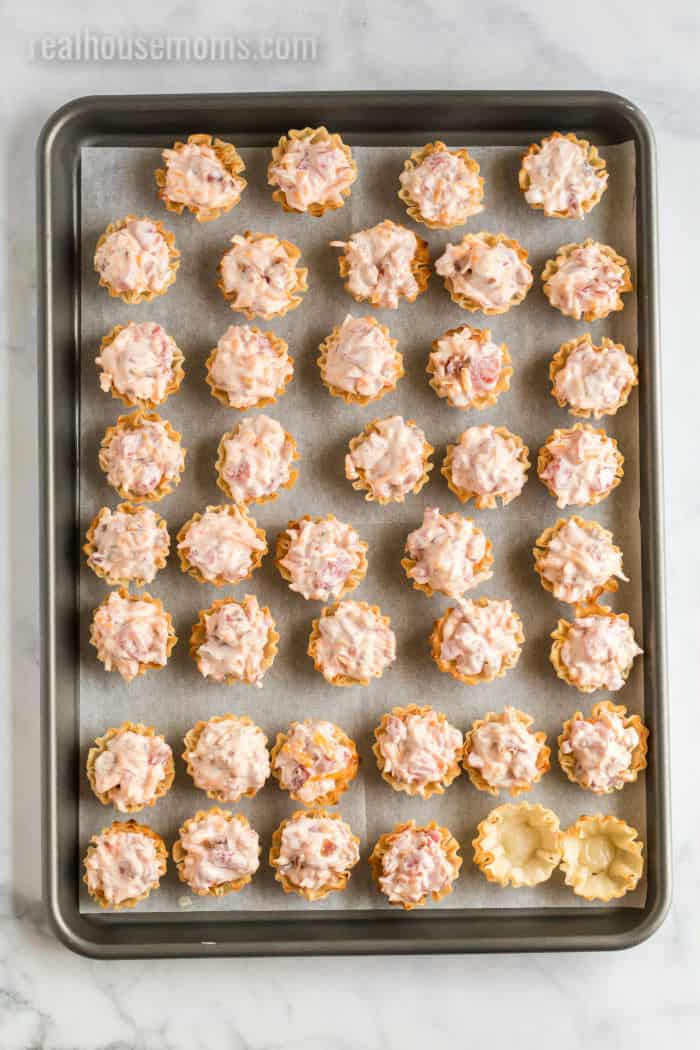mini phyllo shells with filling on a baking sheet