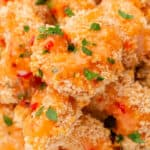square image of bang bang shrimp piled on a plate with extra sauce spooned over the top