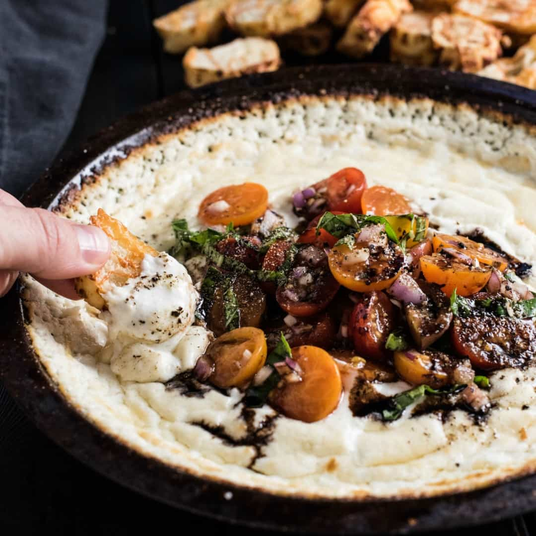 This Baked Goat Cheese Dip is topped with tomatoes, basil, and balsamic and is crazy delicious!