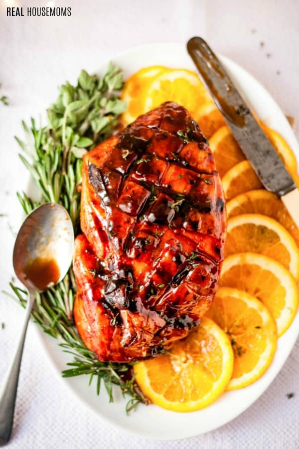 baked ham with brown sugar glaze on a serving platter with oranges and herbs