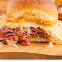 baked reuben slider in front of more sliders on a cutting board with recipe name at bottom