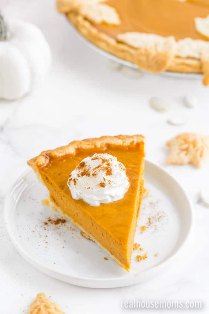 slice of pumpkin pie on a plate topped with whipped cream and cinnamon