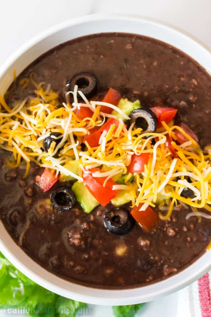 black bean soup topped with tomatoes, avocado, olives, and cheese