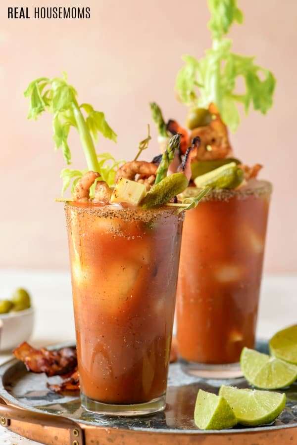 two bloody marys with lime wedges