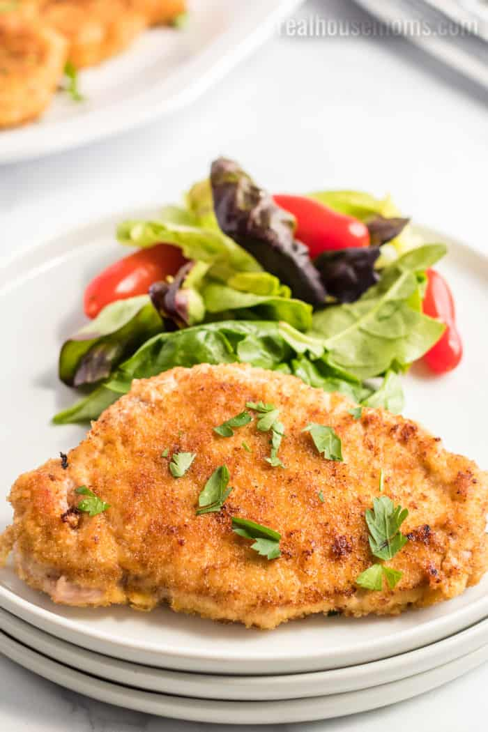 pan-fried breaded pork chop on a plate with salad