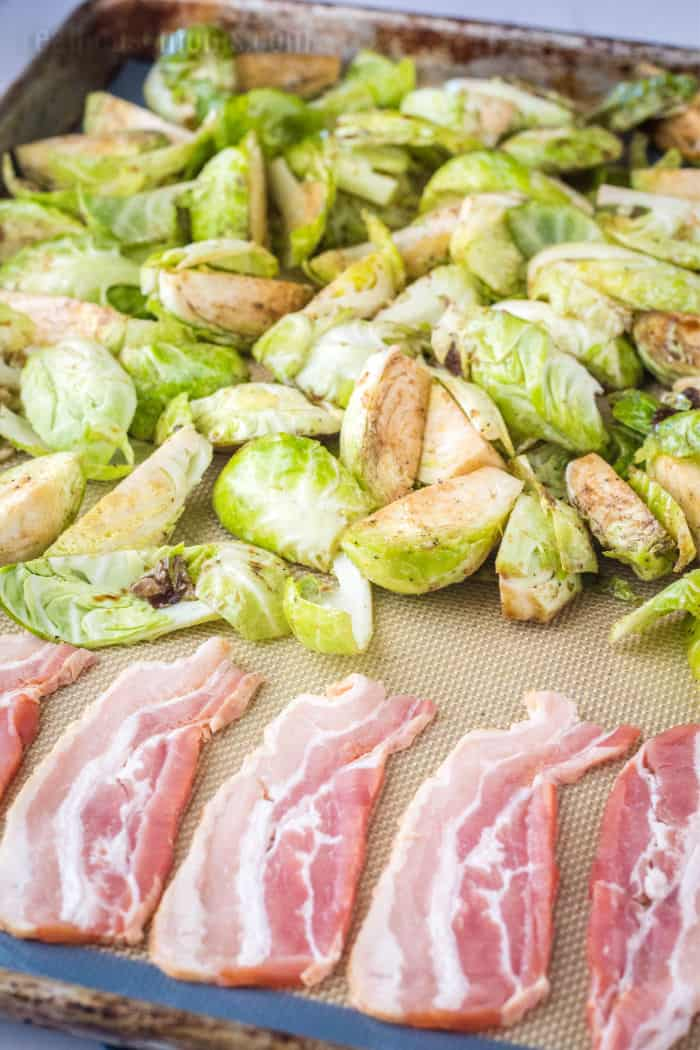brussel sprouts and bacon on a baking sheet before cooking